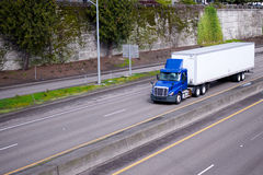 Blue day cab semi truck with dry van trailer moving on highway w Royalty Free Stock Photo