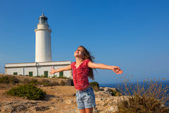 Blue day with kid girl open hands to the wind. In la Mola lighthouse of Formentera Stock Images