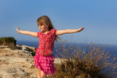 Blue day with kid girl open hands to the wind. And Mediterranean sea Stock Photos