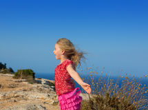 Blue day with kid girl open hands to the wind. And Mediterranean sea Stock Photo