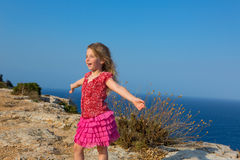 Blue day with kid girl open hands to the wind. And Mediterranean sea Stock Photography
