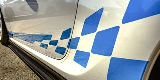 Blue decal on the exterior body of a white car. Close up view of the exterior of a car with bright blue decal on the lower side. Reflection of other cars can stock photos