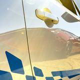 Blue decal on a sunlit white car with reflections. View of a white car`s exterior with decorative blue decals on a sunny day. Reflection of a red car can be stock images