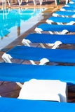 Blue deck chairs arranged around the pool before or after the en Stock Images