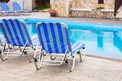 Blue deck chairs at the swimming pool Stock Images