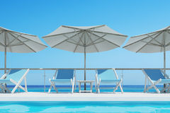 Blue deck chairs, umbrellas, blue sky. Blue deck chairs are standing under beach umbrellas near a swimming pool. A bright blue cloudless sky is above them. Close Stock Photos