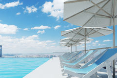 Blue deck chairs, umbrellas, city, side Royalty Free Stock Image