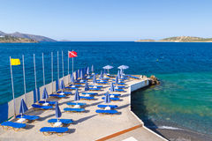 Blue deckchairs under parasol. At Aegean Sea Royalty Free Stock Photo