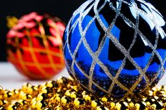Blue christmas ball on golden garland with blurred decorated red ball on background Royalty Free Stock Photo