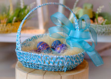 Blue decorated Easter eggs in a basket on a wood stub. Wood decorated blue Easter eggs in a blue basket on a wooden stub with bright colorful defocused Royalty Free Stock Images
