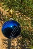 Blue decorative ball on the christmas tree on wooden background. Stock Photo