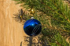 Blue decorative ball on the christmas tree on wooden background. Stock Image