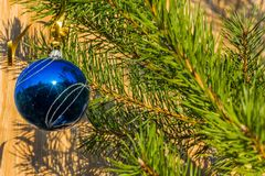 Blue decorative ball on the christmas tree on wooden background. Royalty Free Stock Photos
