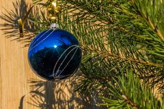 Blue decorative ball on the christmas tree on wooden background. Royalty Free Stock Photo
