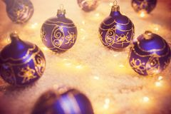Blue decorative Christmas balls and lights in a snow. With some warm lights Stock Photo