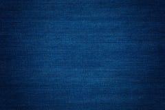 Blue Denim. Dark blue denim background, detailed texture with vignette royalty free stock image