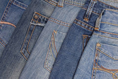 Blue denim background, pile of  jeans, back side. Blue denim background, pile of different jeans, back side Royalty Free Stock Photo