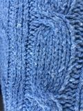 Blue denim colour cable knit blanket texture. Blue denim colour close up of cable knit blanket in cotton mix wool. Quite a rough texture to the touch Royalty Free Stock Photos