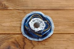 Blue denim floral brooch or hair accessory  on a wooden table. How to Recycle old jeans into a new jewelry Stock Image