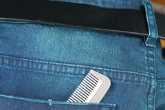 Blue denim jeans in dark color with comb in the scene present th Royalty Free Stock Photos