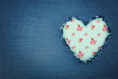 Blue denim jeans with green heart. Green floral vintage heart shape for copy space torn from blue denim jeans fabric, romantic love concept background royalty free stock photography