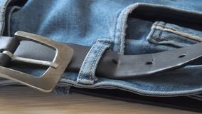 Blue denim jeans laying on the table. Macro dolly shot. Selective soft focus. Camera moving along leather belt. Clothing. For everyday wearing. Blue trousers stock footage