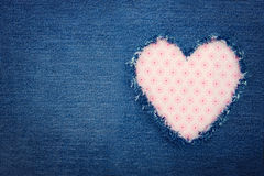 Blue denim jeans with pink heart. Pink heart shape torn from blue denim jeans fabric with copy space, romantic love concept background stock images