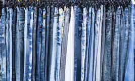 Blue Denim Jeans. A rack of a variety of blue denim jeans in various shades of blue. Texture, patterns and variety stock image