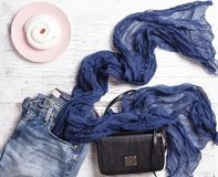 Blue denim jeans, blue scarf, handbag and pink plate with white cake. Flat lay, top view. Royalty Free Stock Photos