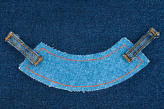 Blue denim jeans tag label lying on dark jeans. Royalty Free Stock Photos