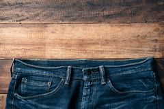 Blue denim jeans on wooden table. Fashion concept with copy space Royalty Free Stock Images