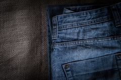 Blue denim pants are on the background of old linen burlap. Abstract background Royalty Free Stock Images
