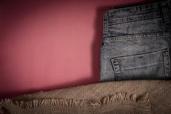 Blue denim pants are on the background of old linen burlap royalty free stock photography