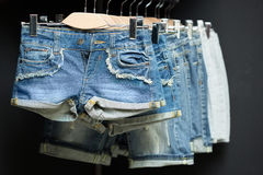 Blue denim shorts on a hanger Stock Images