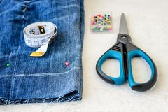 Blue denim shorts, roll of tailor tape with centimeters and inches, multi coloured headed sewing pins in a box and scissors. Making denim shorts. On a white stock photography