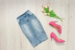 Blue denim skirt, pink shoes and bouquet of tulips. Fashionable Stock Photos