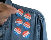 Blue denim working clothing with many Voted stickers on white background royalty free stock photos
