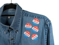 Blue denim working clothing with many Voted stickers on white background stock photos