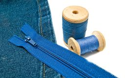 Blue denim with zipper and spools of thread Stock Photos