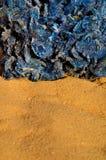 Blue desert rose 2. Piece of Sahara - mineral blue desert rose and yellow Sahara sand background, close up, vertical orientation Stock Images