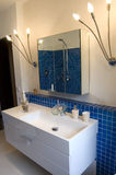 Blue Designer Bathroom. Modern bathroom with blue tiles, stylish basin and large mirror Stock Photos