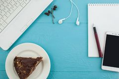 Desktop, laptop, phone and a piece of cake. Blue desktop, white laptop, phone and a piece of cake Stock Images