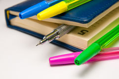 Blue diary and mechanical pencil within and few color pens Royalty Free Stock Photos