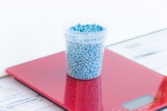 Blue different shape chemical fertilizer granules in glass on red scales.