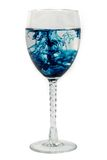 Blue diffusion in a glass. Blue dye diffusion in a wine glass Royalty Free Stock Image