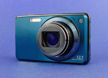 Blue digital camera. Stylish blue compact pocket digital camera over blue background Royalty Free Stock Photo