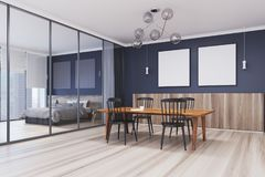Blue dining room corner, table and two posters. Blue dining room corner with a wooden floor, two square posters and a table with chairs under them. 3d rendering Stock Photo