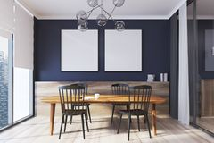 Blue dining room interior, square posters. Blue dining room interior with two square posters hanging above a wooden table with black chairs. 3d rendering mock up Royalty Free Stock Photo