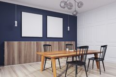 Blue dining room, table and two posters side. Blue dining room interior with a wooden floor, two square posters and a table with chairs under them. A side view Royalty Free Stock Photography