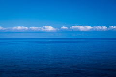 Blue dipp. Impressive interesting clouds, sea painted in evenings intense deep blue color Stock Images